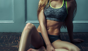 Beautiful athletic tanned blonde woman sitting on floor
