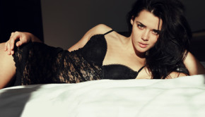 woman with dark hair in lace lingerie dress lying in bed in the morning