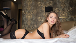 Sexy brunette woman lying on a bed in black lingerie